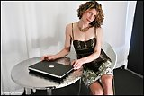 Tgirl Delia in tan stockings with laptop